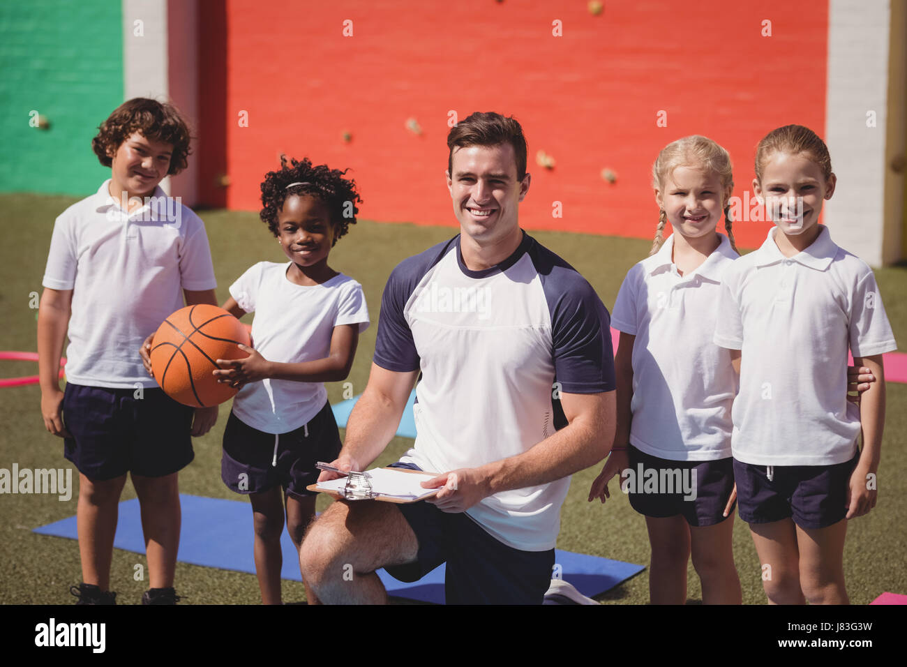 Portrait of happy coach and schoolkids in schoolyard - Stock Image