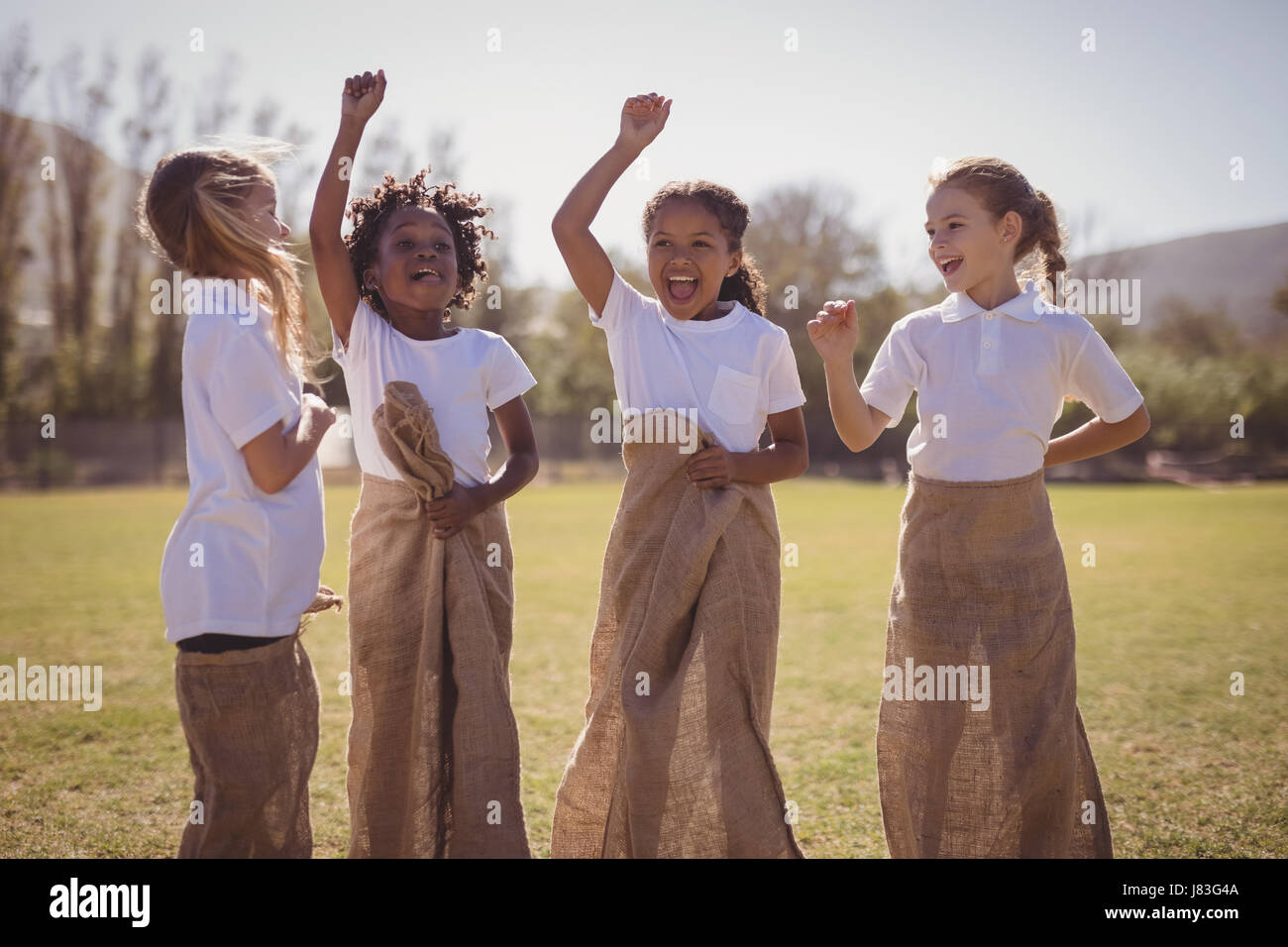 Happy schoolgirls standing in sack during race on a sunny day - Stock Image