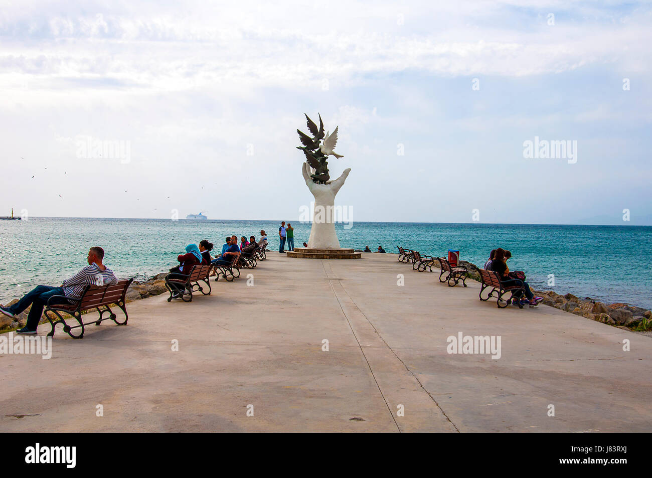 Unidentified Turkish people relax around the Hand Of Peace Monument in Kusadasi, Aegean Coast, Turkey - Stock Image