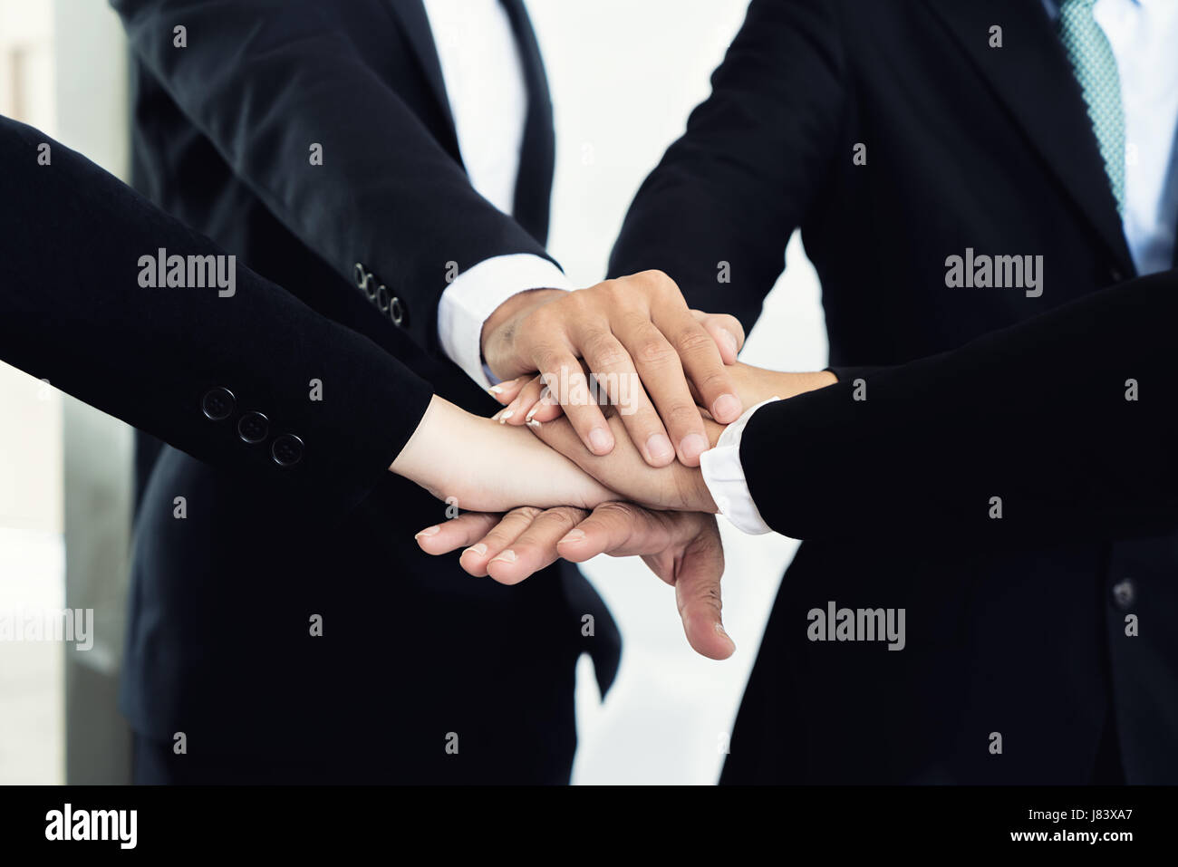 Close up of business partners making pile of hands at meeting. Business people collaboration teamwork union concept. - Stock Image