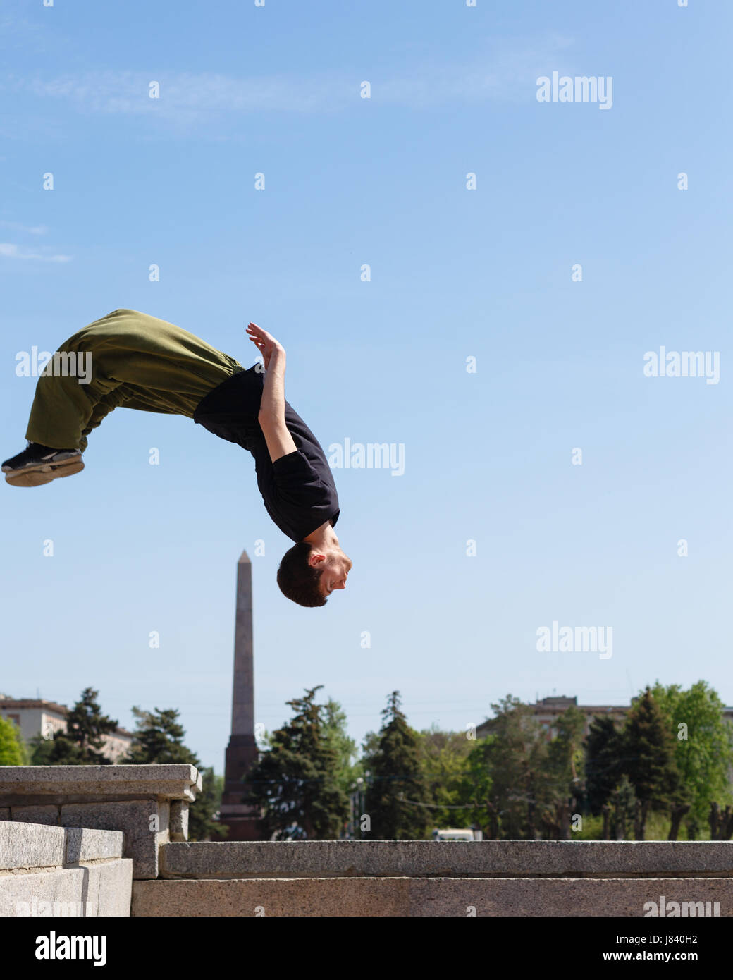 Young man doing a back flip in the background obelisk. Parkour in the urban space. Sports in the city. Sport activity. - Stock Image