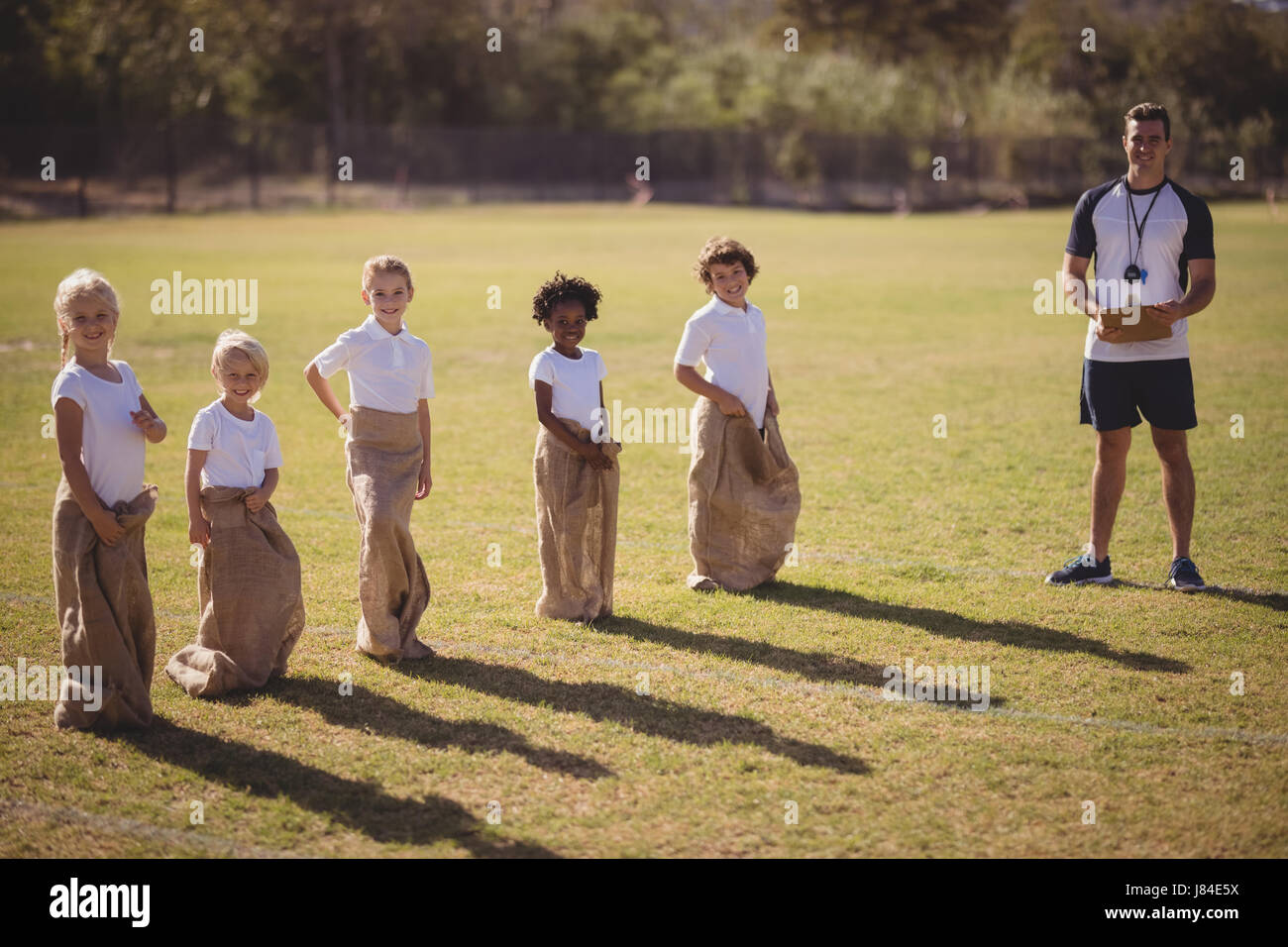 Portrait of coach and schoolgirls standing in park during sack race on a sunny day - Stock Image