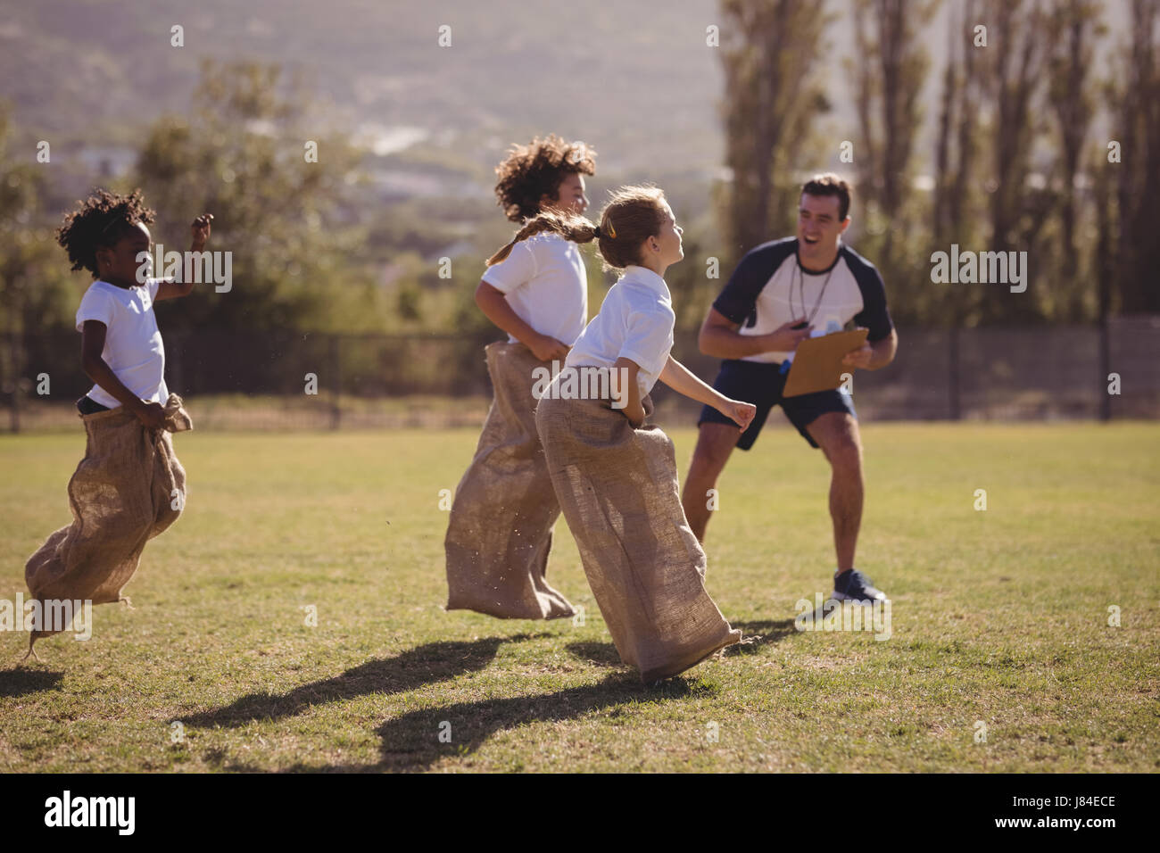 Coach cheering schoolgirls during sack race in park on a sunny day - Stock Image