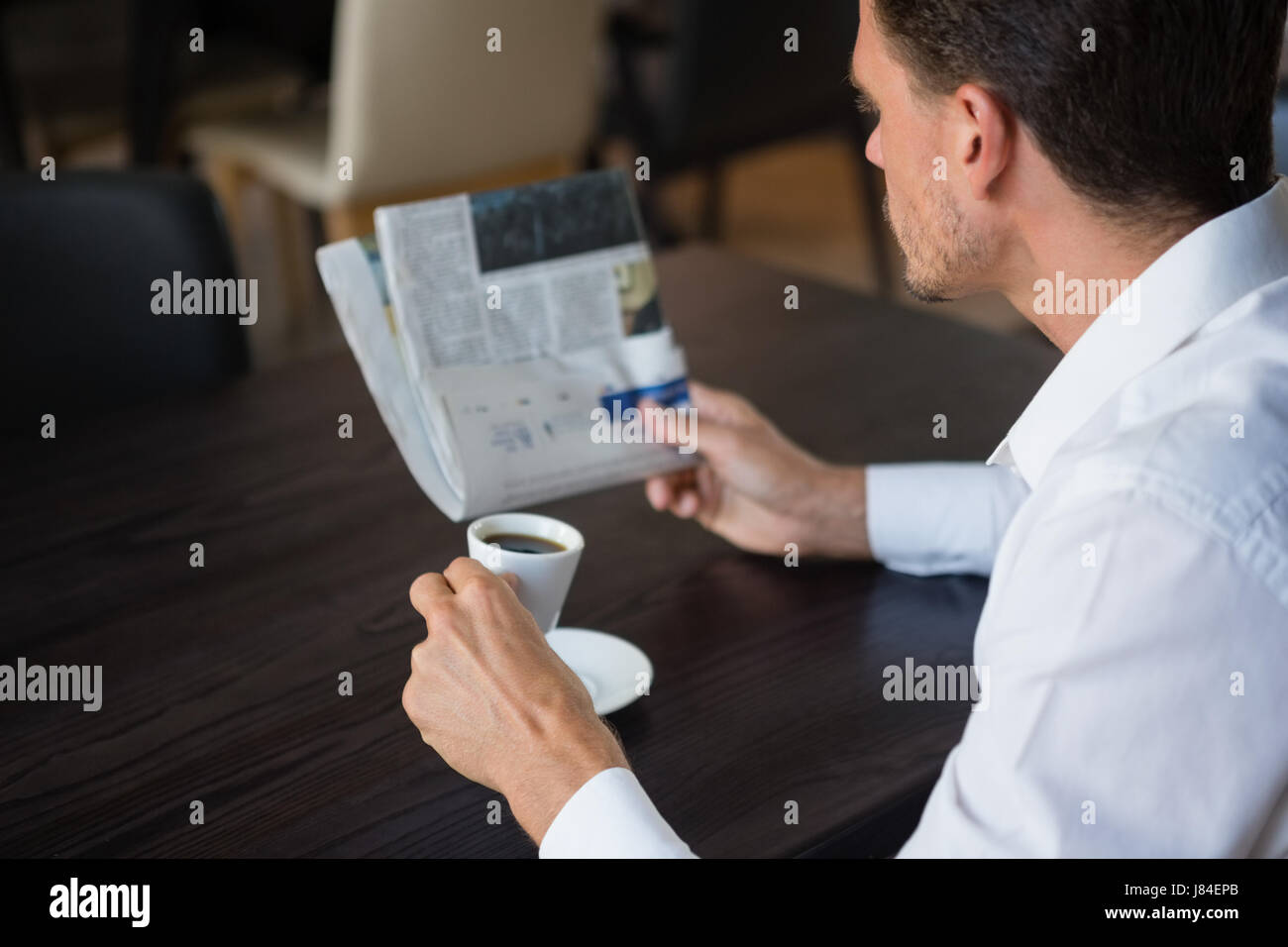 Businessman reading newspaper while having coffee at table in cafe - Stock Image
