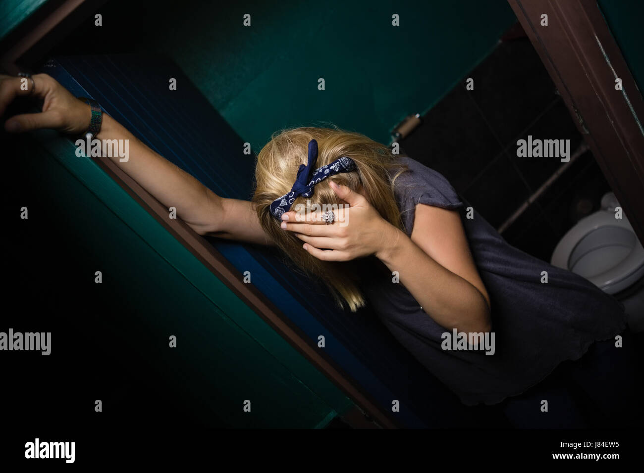 Unconscious drunk woman standing in the washroom Stock Photo