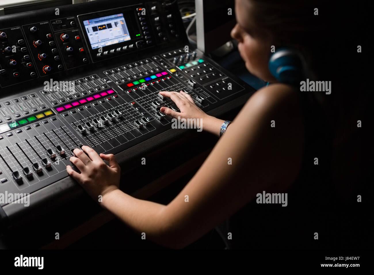 Female audio engineer using sound mixer in recording studio Stock Photo