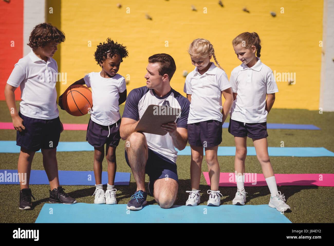 Coach and schoolkids discussing on clipboard in schoolyard - Stock Image