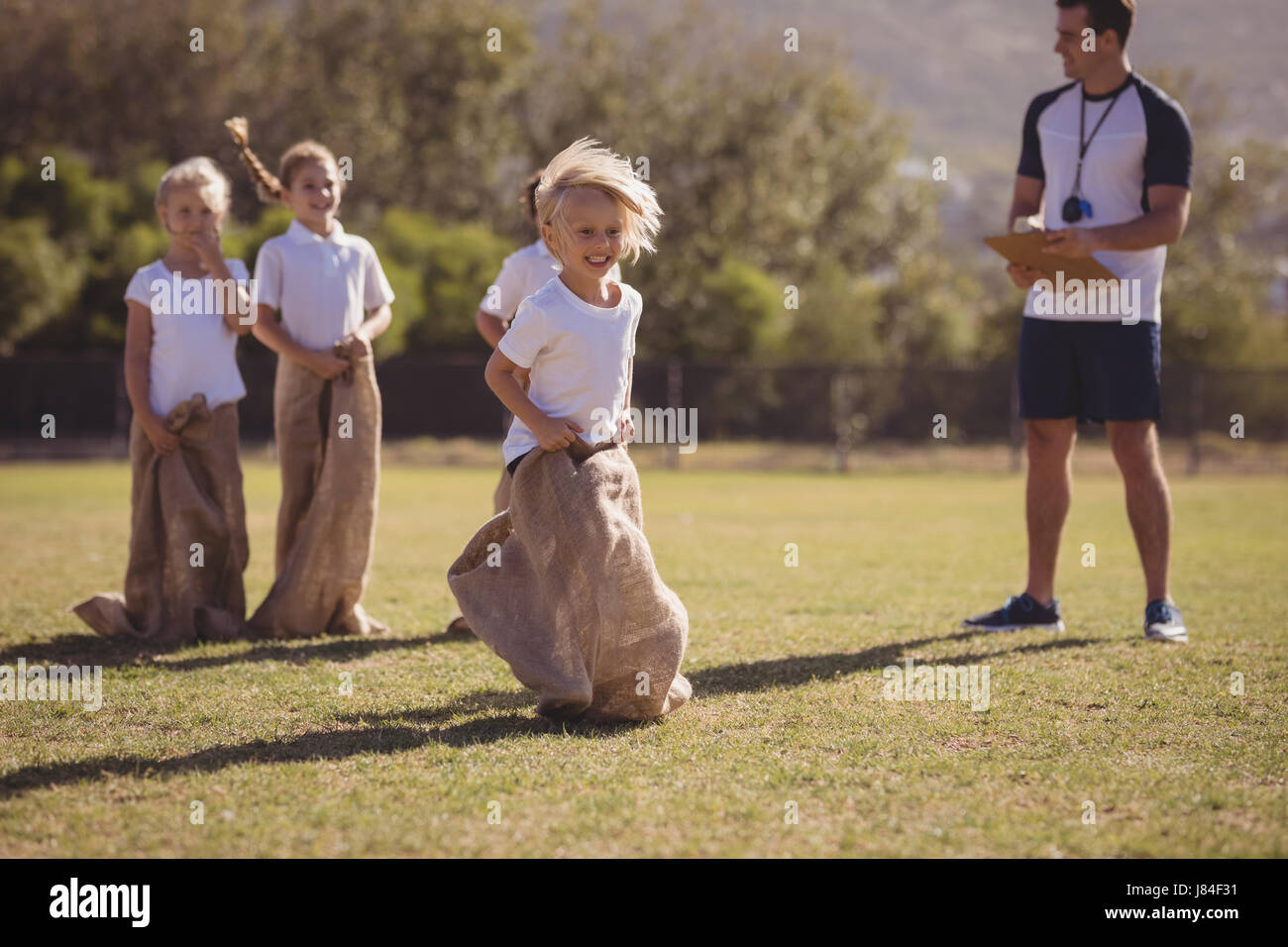 Coach monitoring schoolgirls during sack race in park on a sunny day - Stock Image
