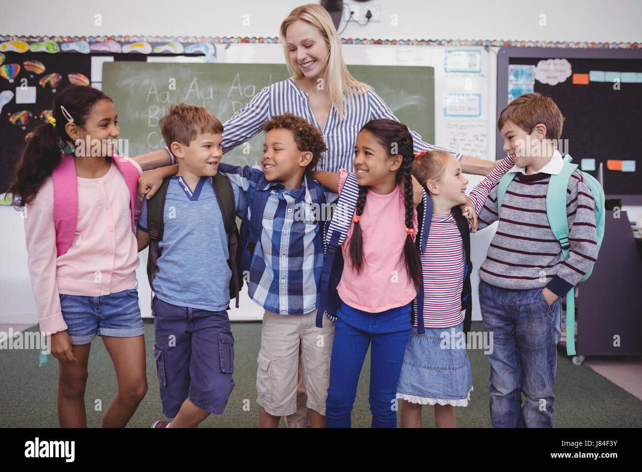 Happy teacher standing with schoolkid in classroom at school - Stock Image