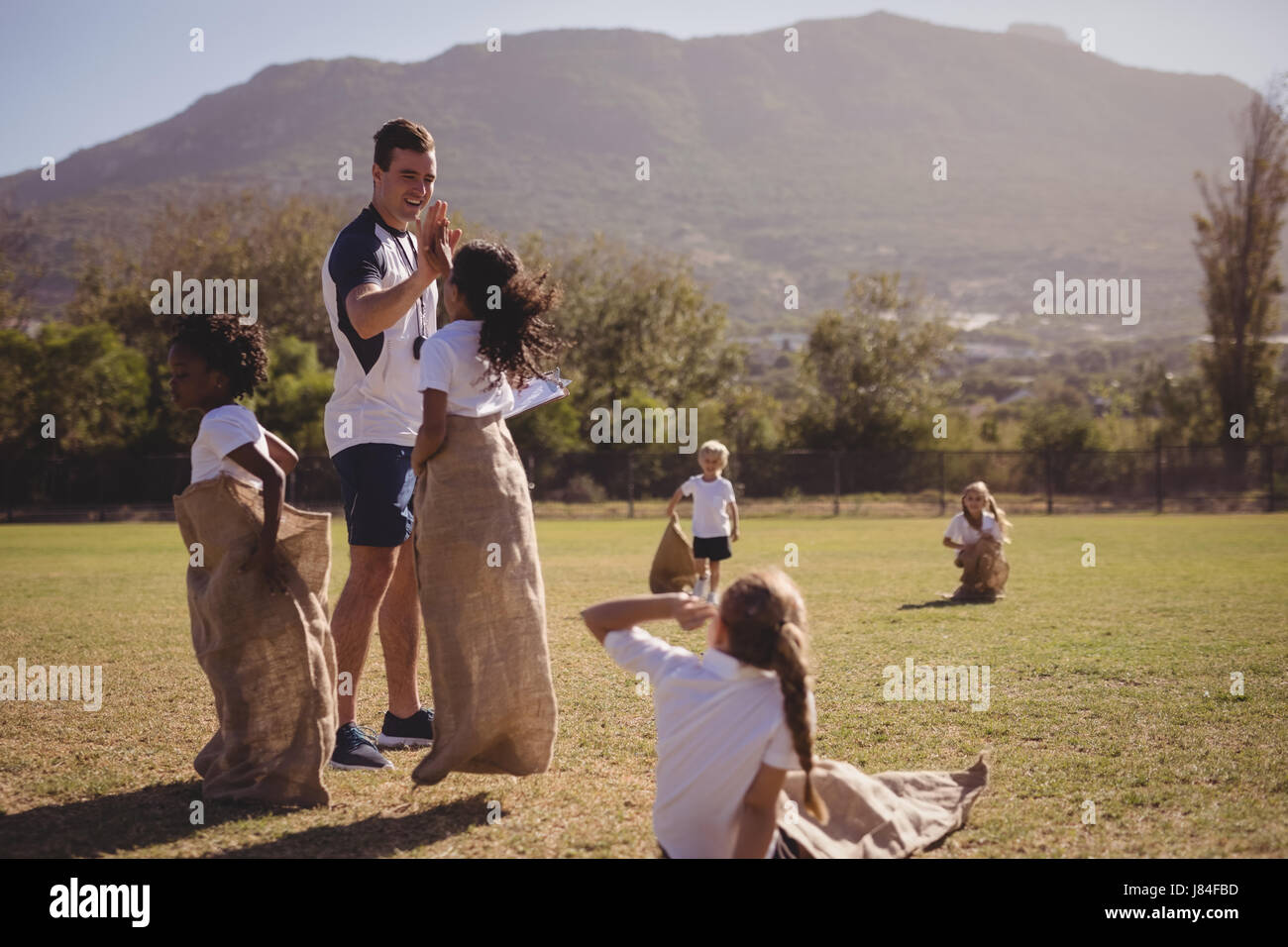 Coach and schoolgirl giving high five to each other during sack race on a sunny day - Stock Image