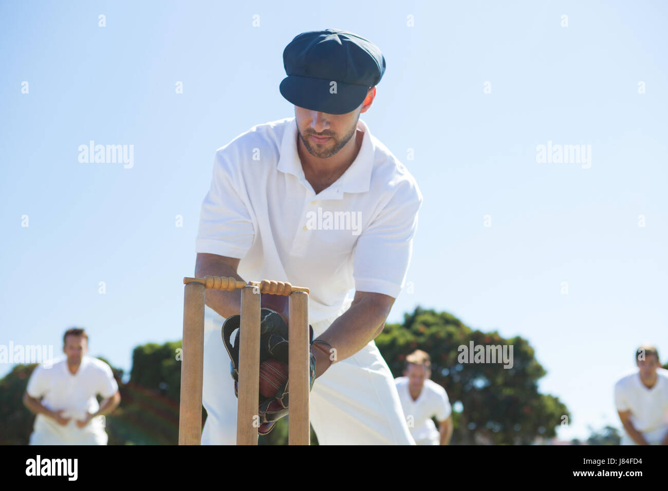 Close up of wicket keeper standing by stumps against clear sky - Stock Image