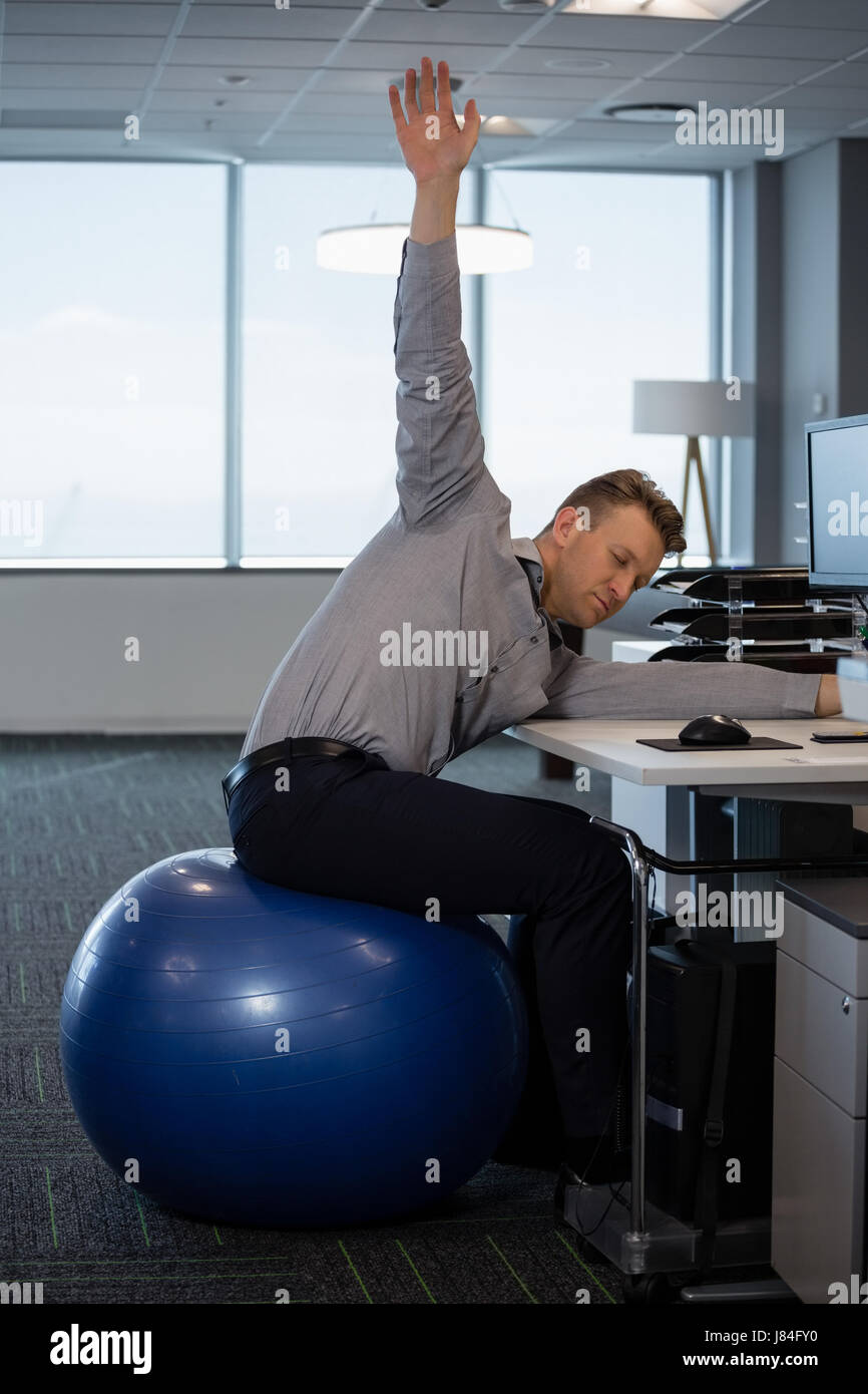 Executive Performing Stretching Exercise On Fitness Ball In Office Stock Photo Alamy