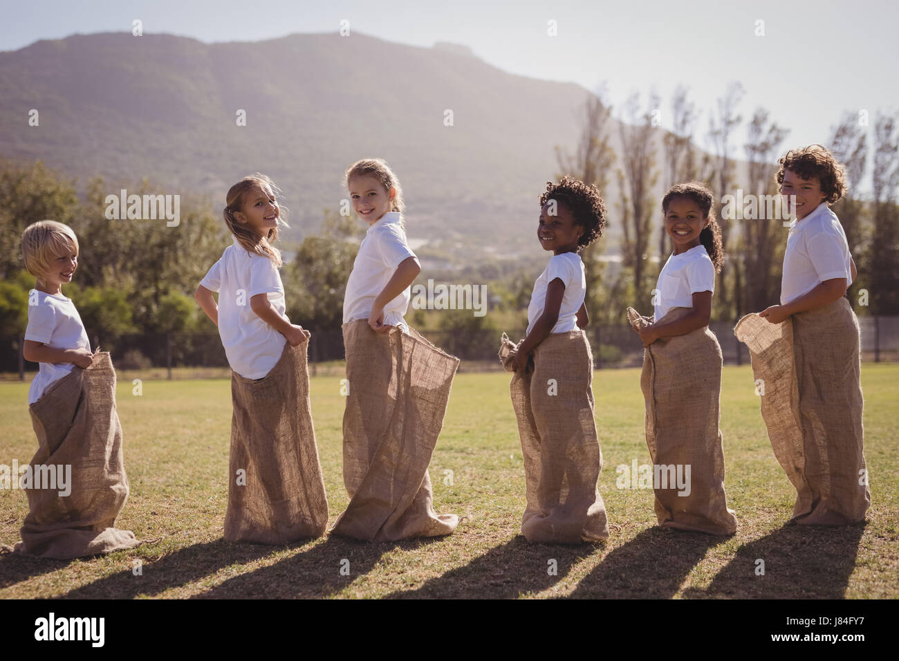 Schoolgirls having fun during sack race in park on a sunny day - Stock Image