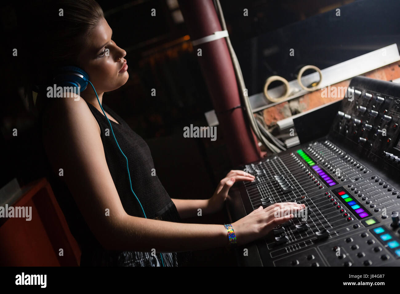 Female audio engineer using sound mixer in recording studio Stock Photo