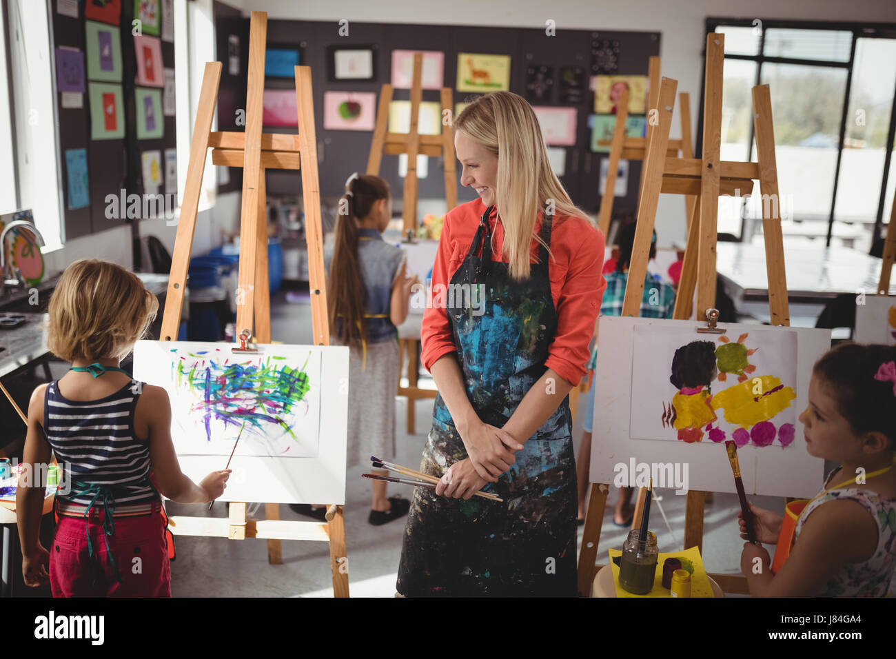 Teacher assisting schoolkid in drawing class at school - Stock Image