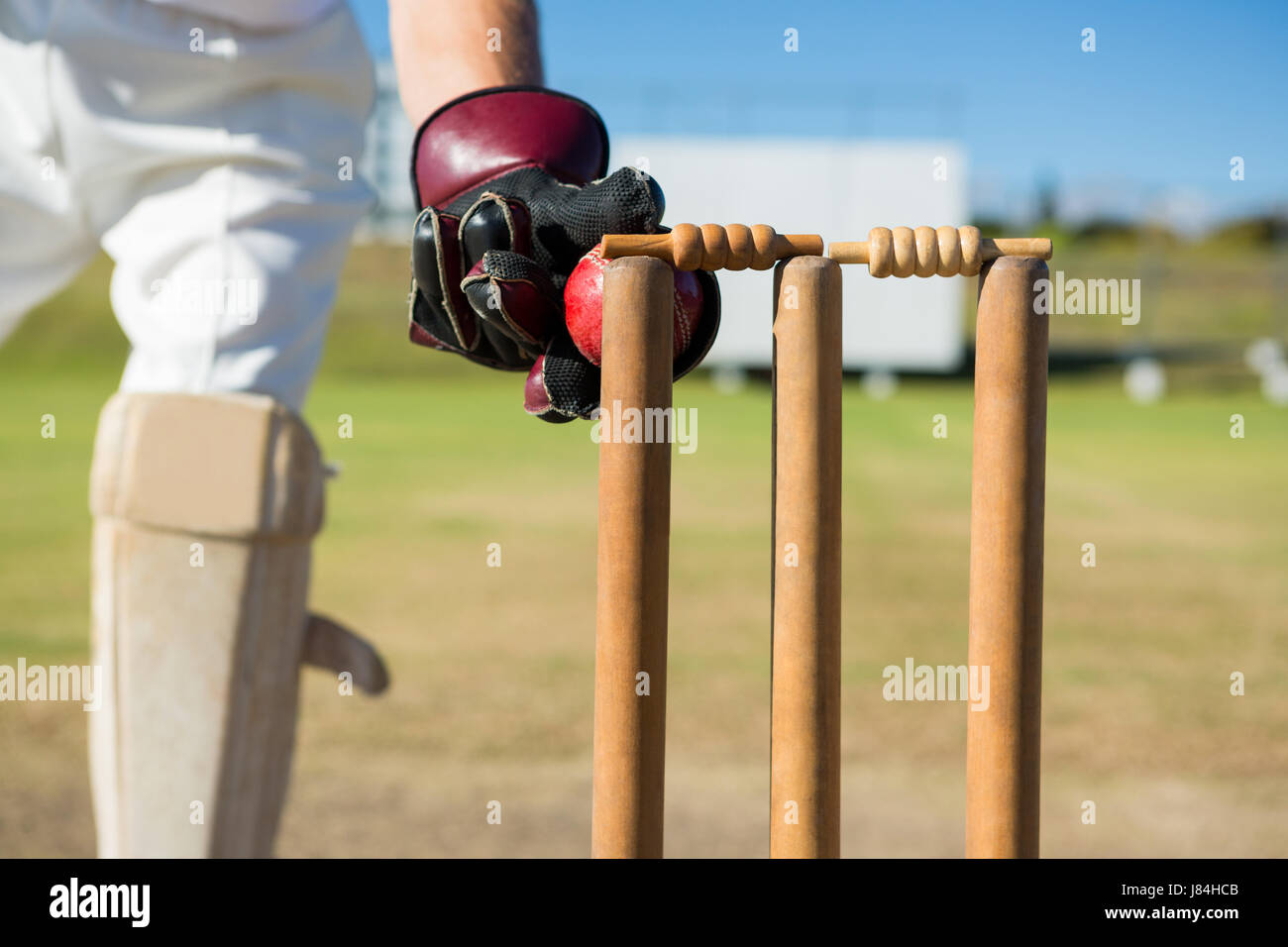 Close up of wicket keeper standing by stumps during match on sunny day - Stock Image