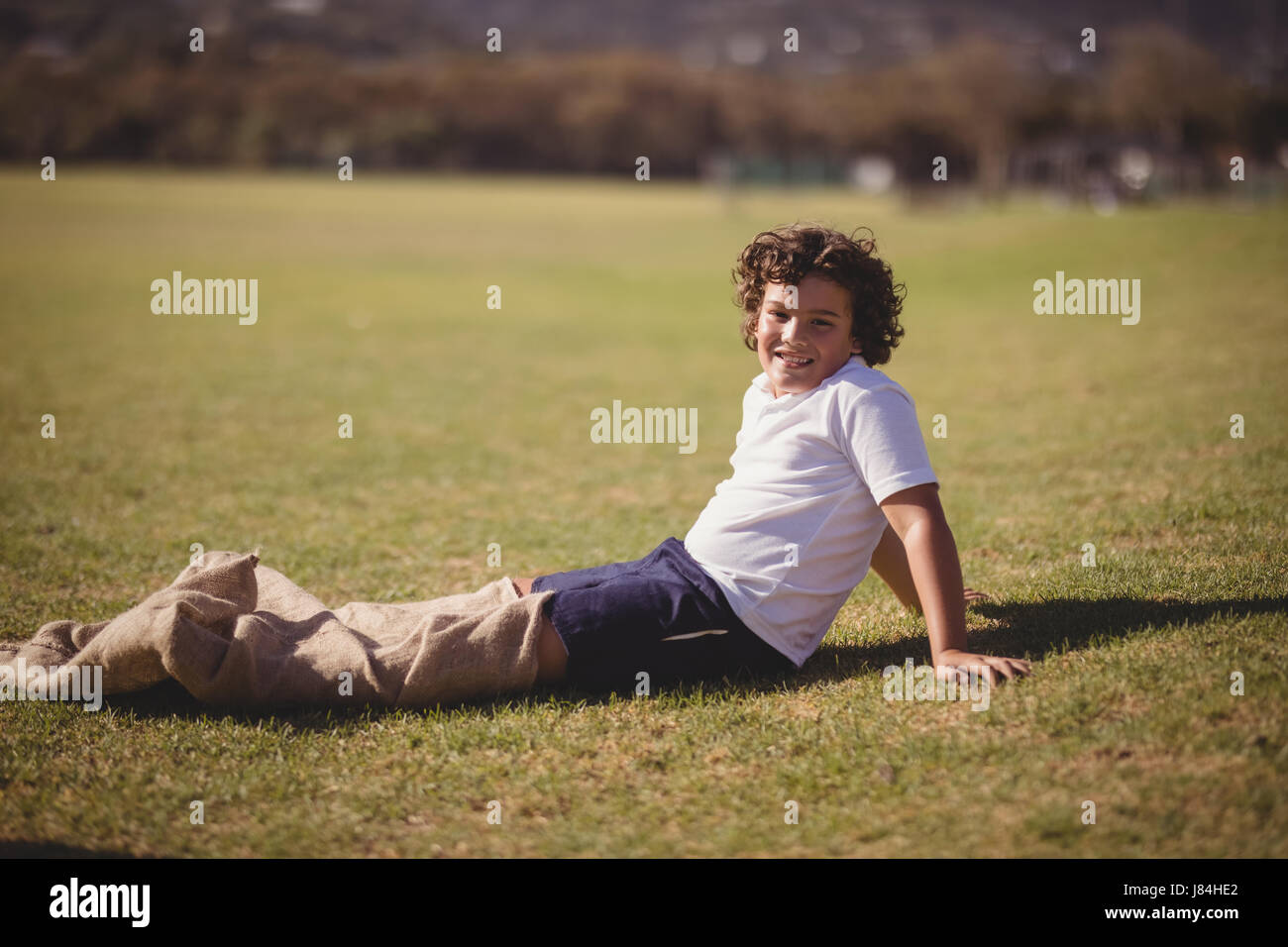 Portrait of happy schoolgirl preparing for sack race in park on a sunny day - Stock Image