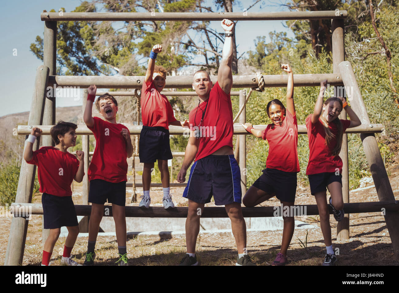 Portrait of trainer and kids standing together in the boot camp - Stock Image