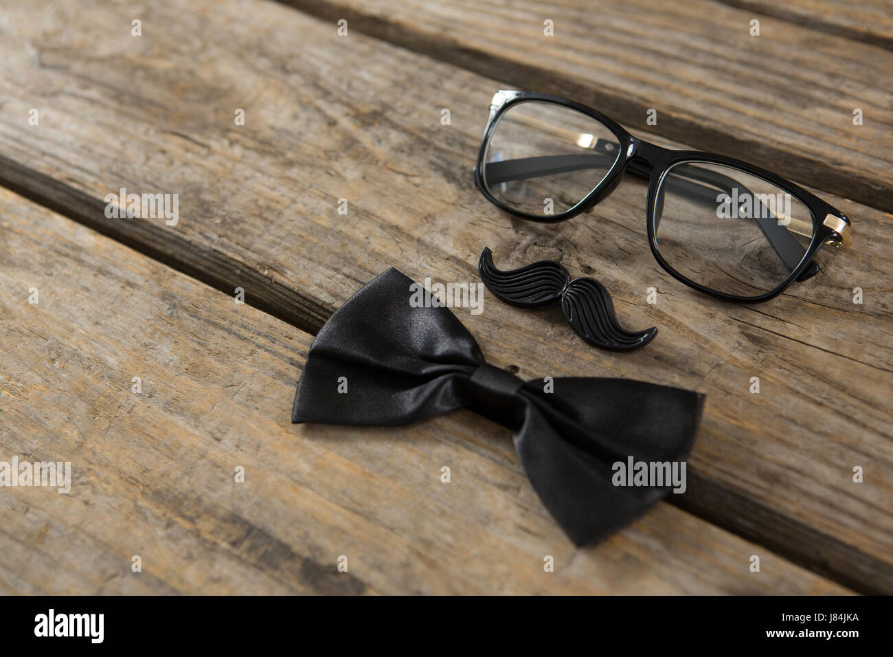 High angle view of bow tie with mustache and eyeglasses on wooden table - Stock Image