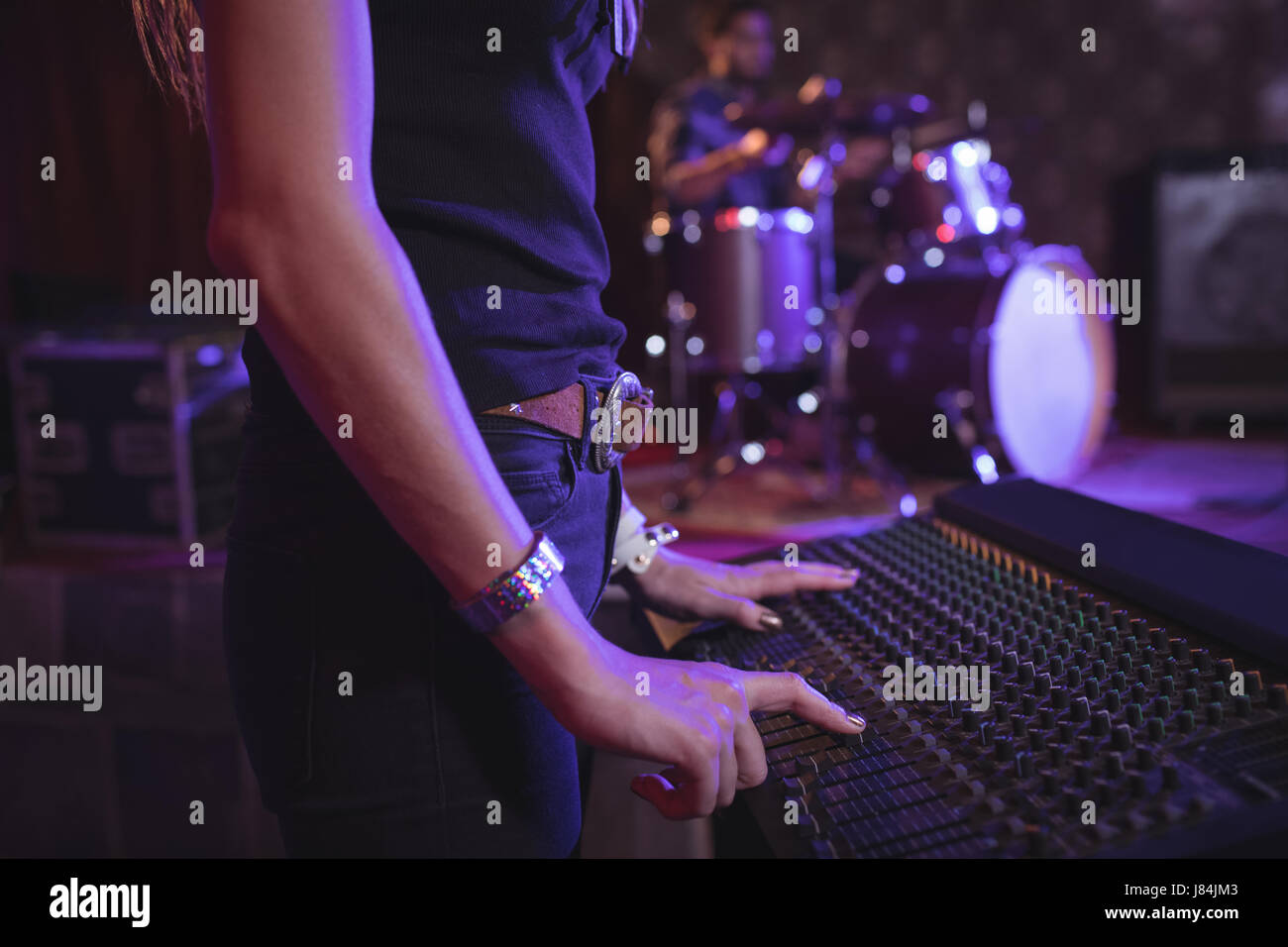 Mid section of female musician operating sound mixer in nightclub - Stock Image