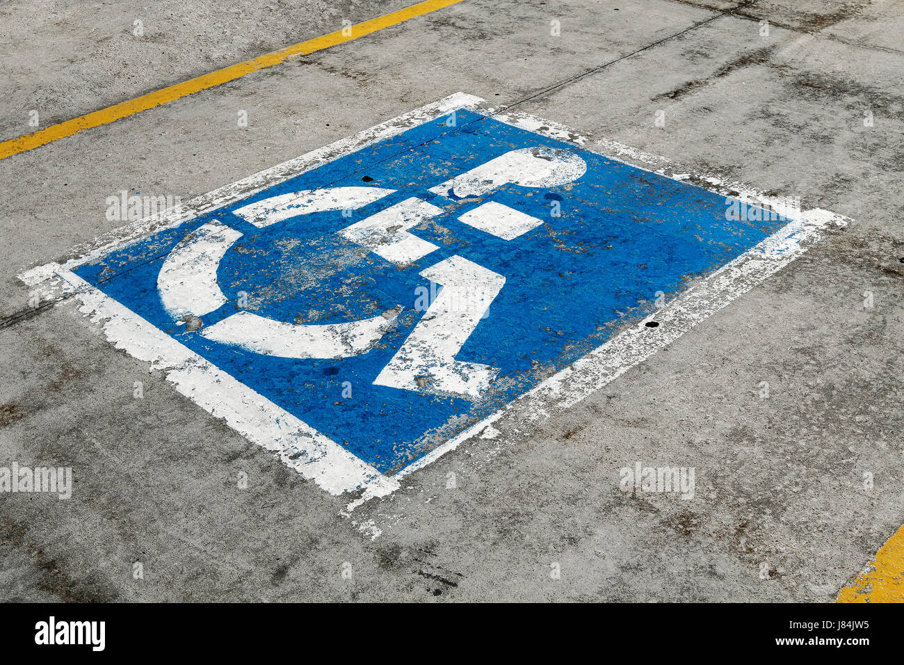 Worn out sign for handicapped parking spot. - Stock Image