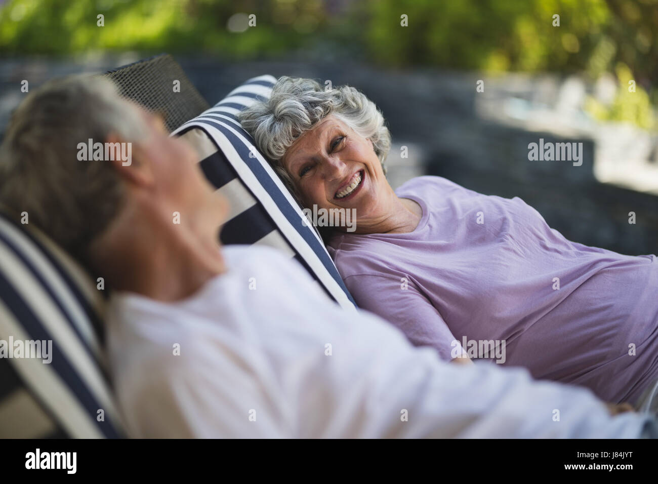 Smiling senior woman looking at man resting together on lounge chairs - Stock Image