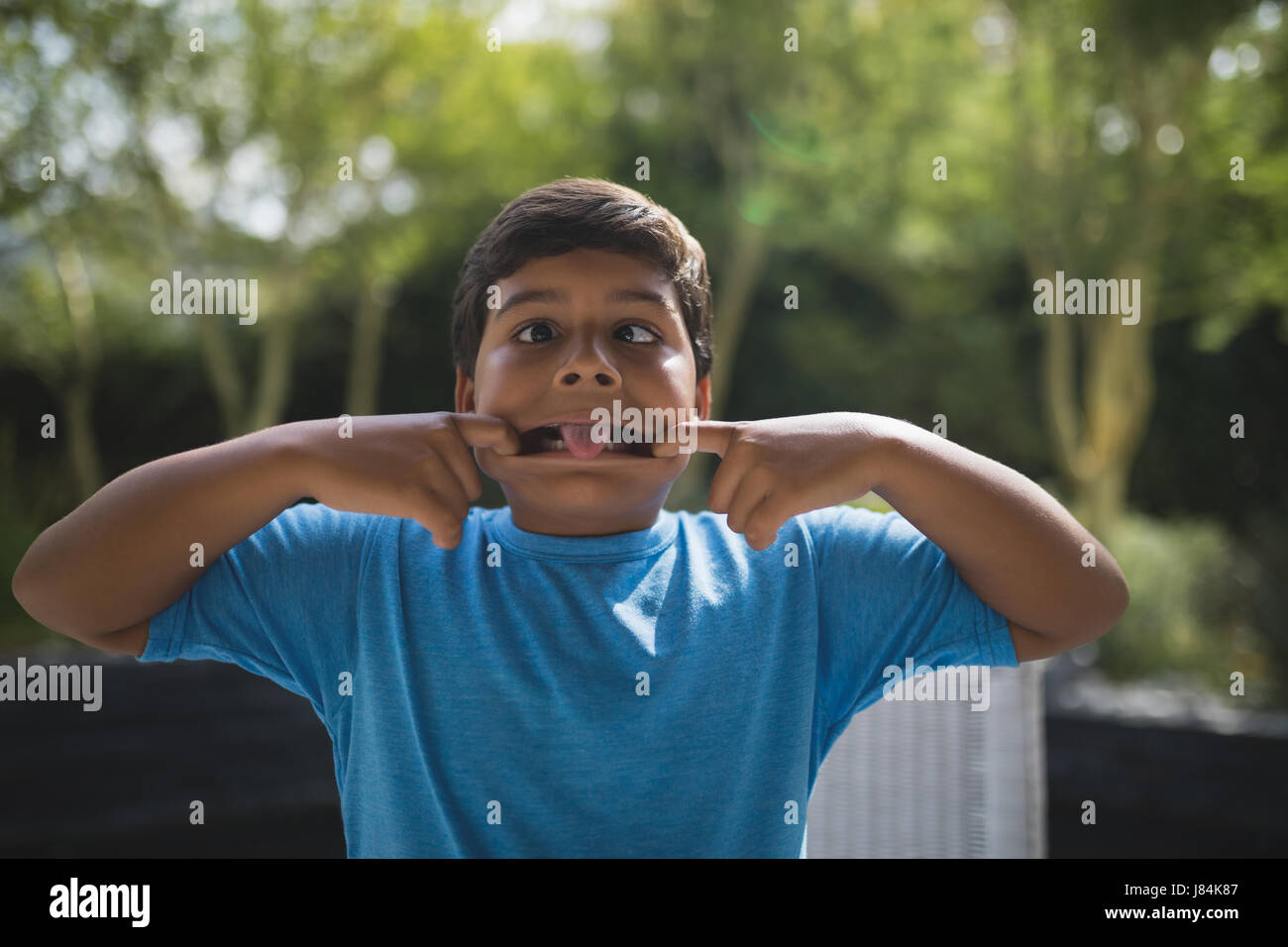 Playful boy teasing while standing at park - Stock Image
