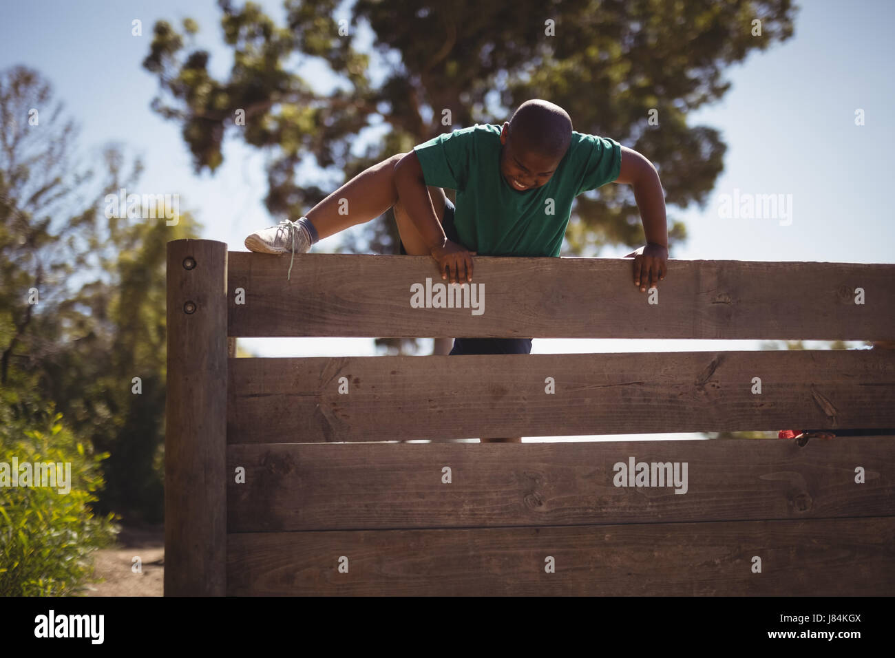 Boy climbing wooden wall during obstacle course in boot camp - Stock Image