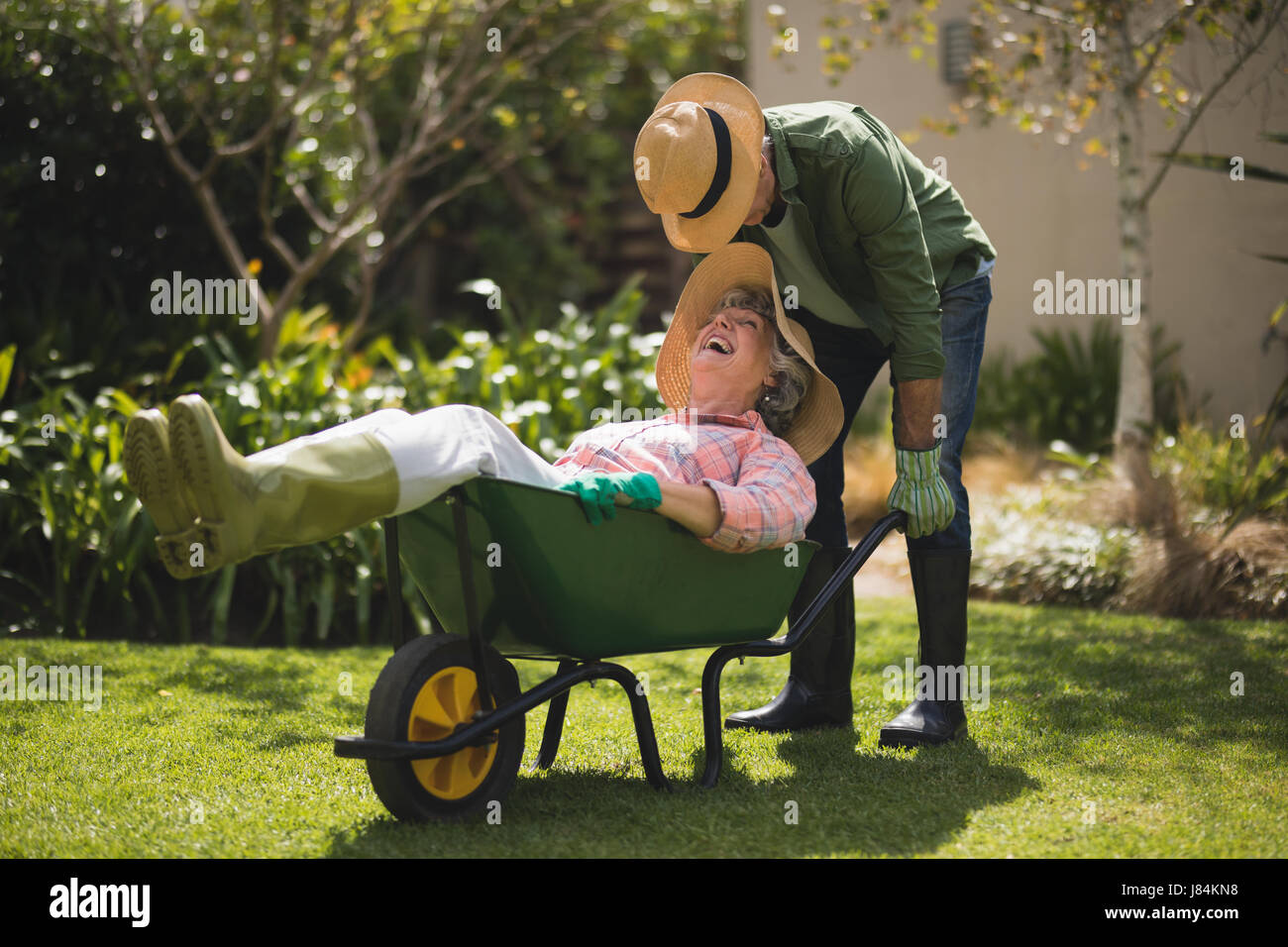 Senior man carrying smiling woman in wheel borrow at yard - Stock Image