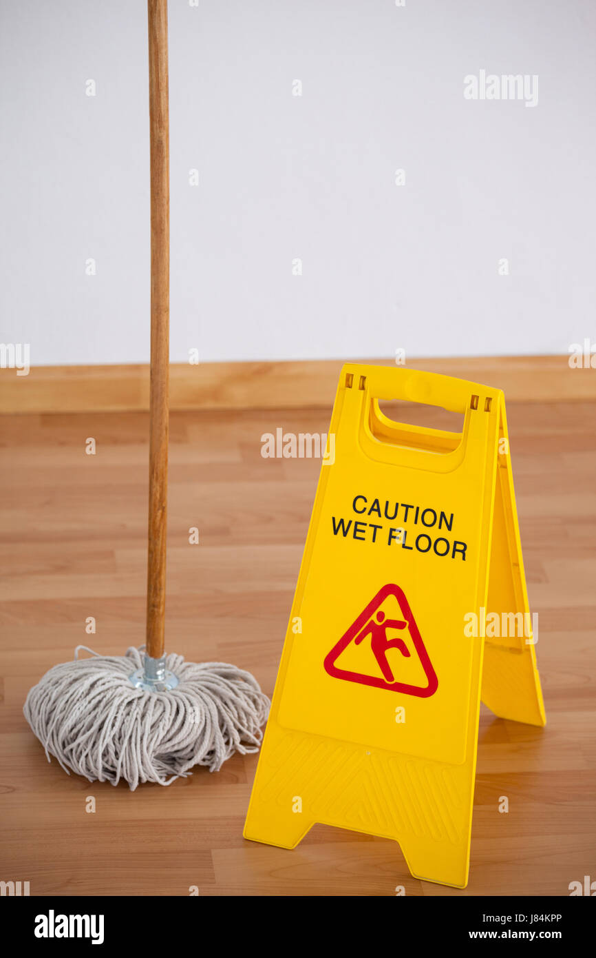 Mop with wet floor caution sign on wooden floor Stock Photo