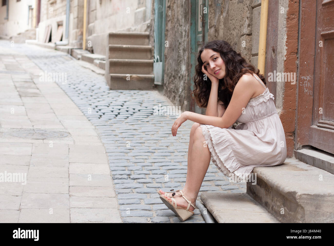 Young curly girl wearing romantic biege dress sitting in front of wooden brown door on narrow streets of old downtown - Stock Image