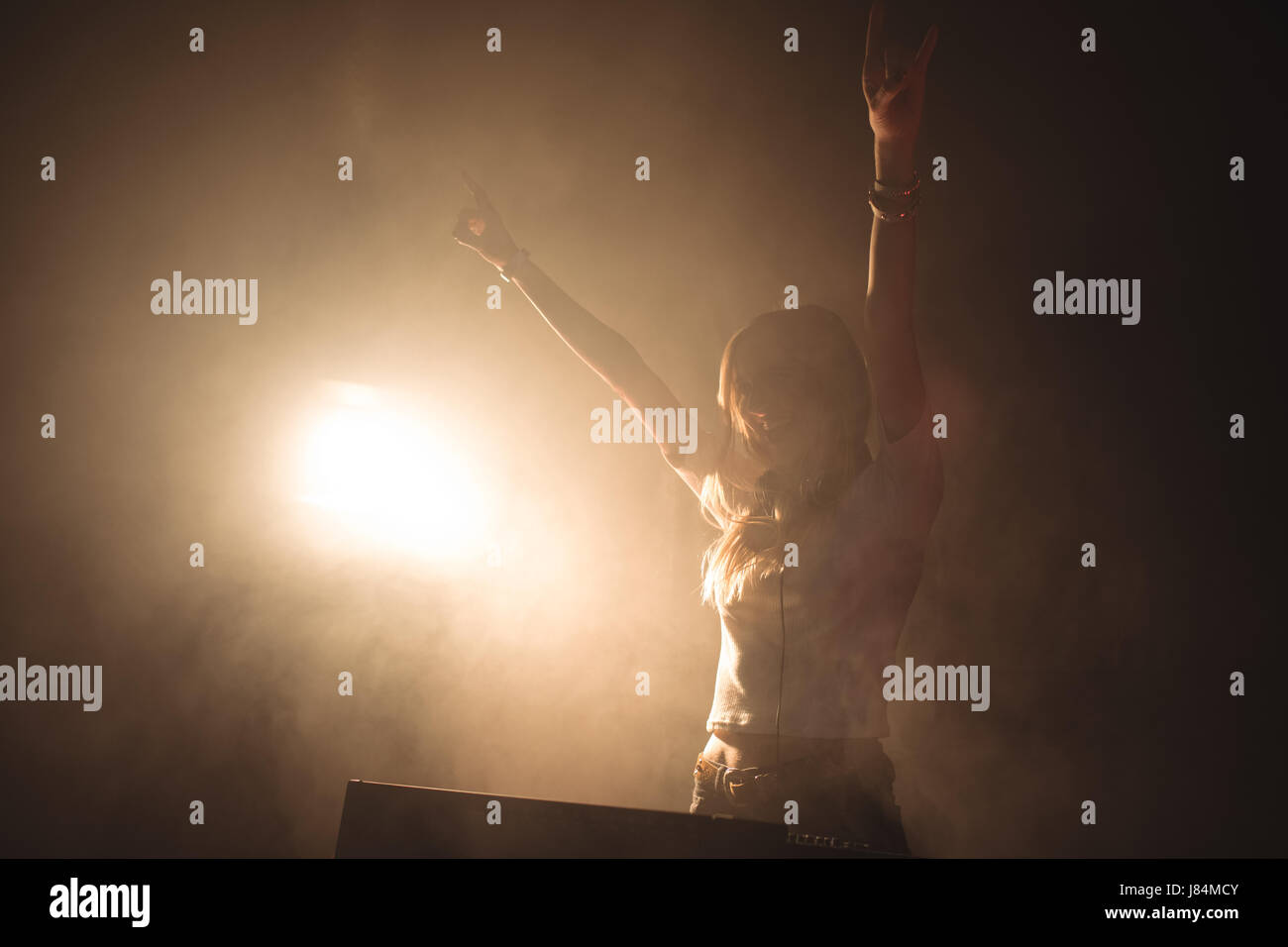 Enthusiastic female DJ playing music in illuminated nightclub - Stock Image