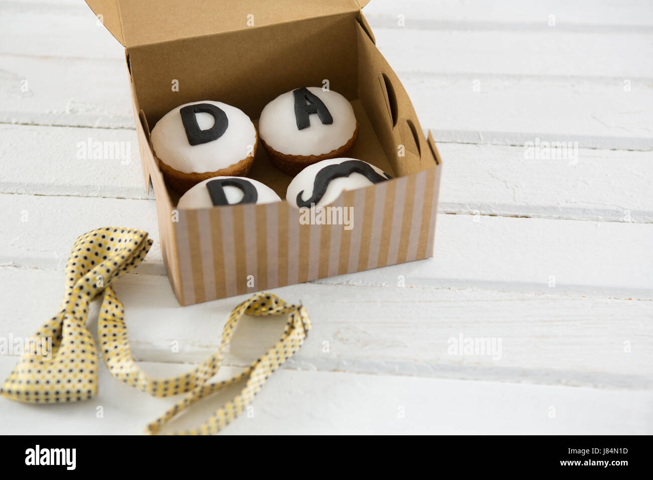 High angle view of cupcakes in container by bow tie on wooden table - Stock Image