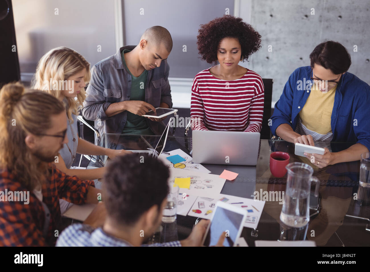 High angle view of business team working together at creative office desk - Stock Image