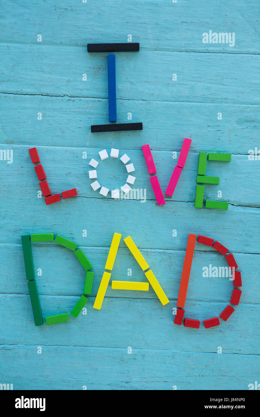 Overhead view of multi colored i love dad text on blue table - Stock Image