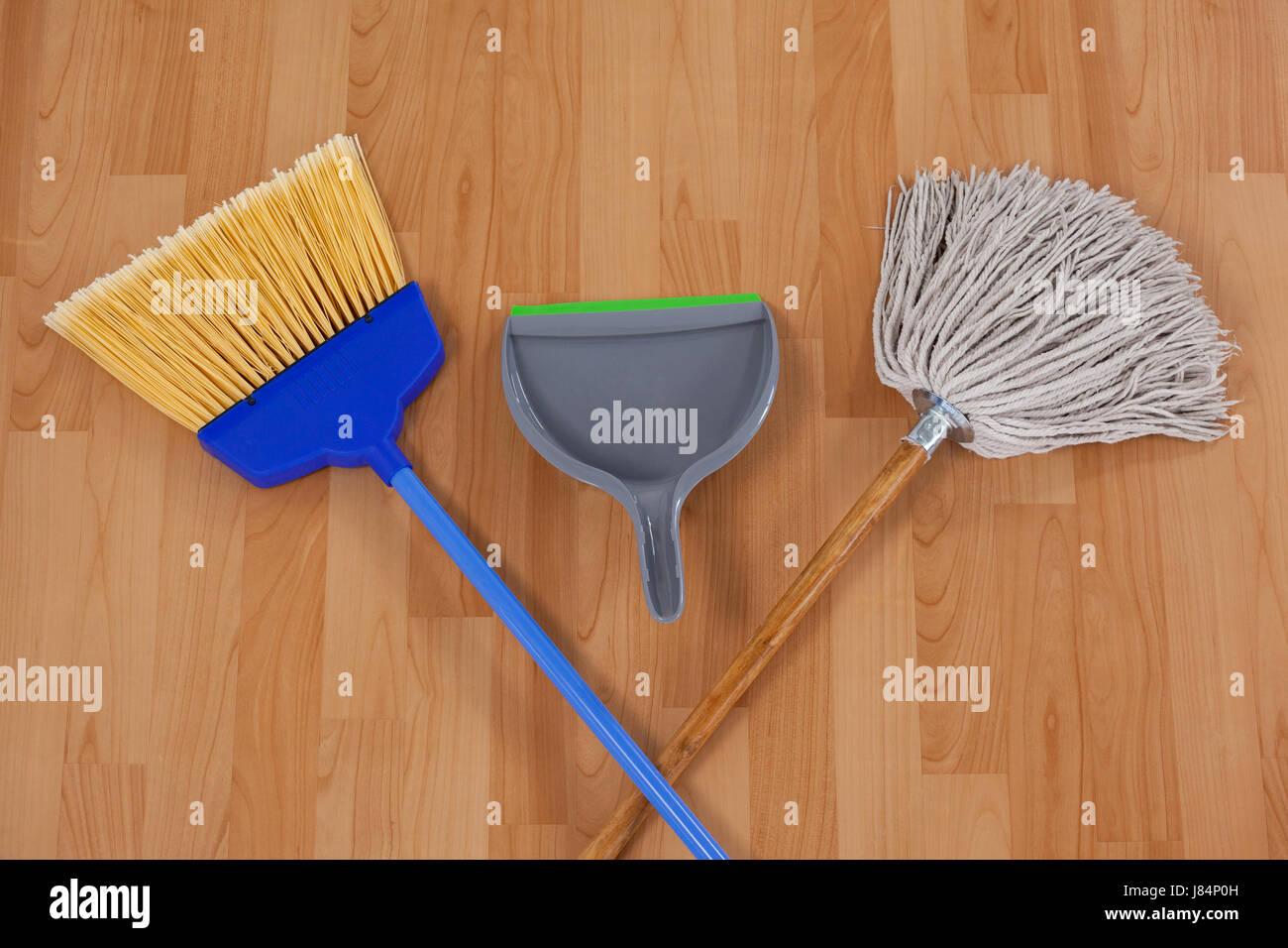 Dustpan, sweeping broom and mop on wooden floor - Stock Image