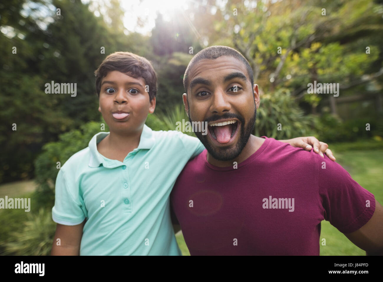Portrait of mischievous father and son enjoying at park - Stock Image