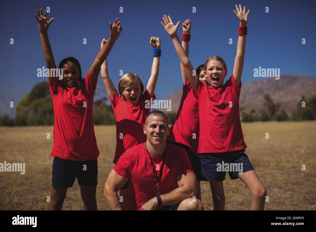 Portrait of trainer and kids relaxing in the boot camp - Stock Image