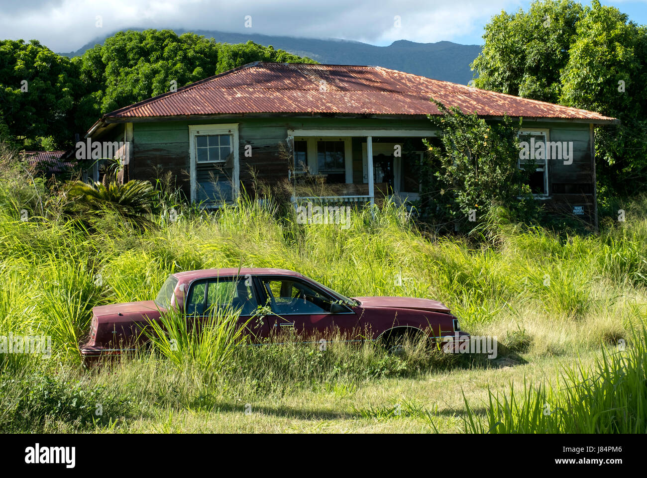 an abandoned car sits in a yard next to a derelict property just off the Pi'ilani Highway in south Maui, Hawaii - Stock Image