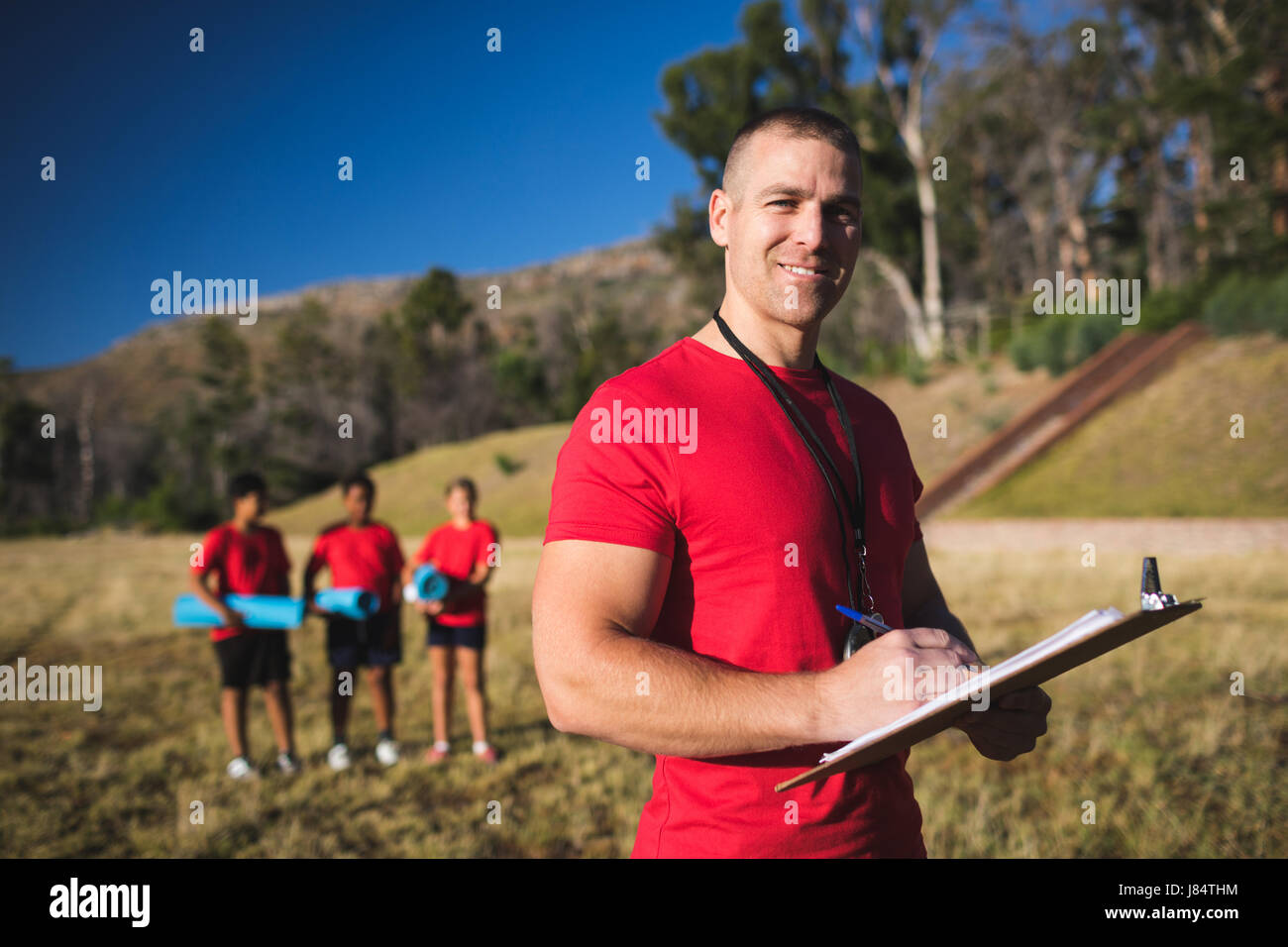 Portrait of trainer writing on clipboard in the boot camp - Stock Image