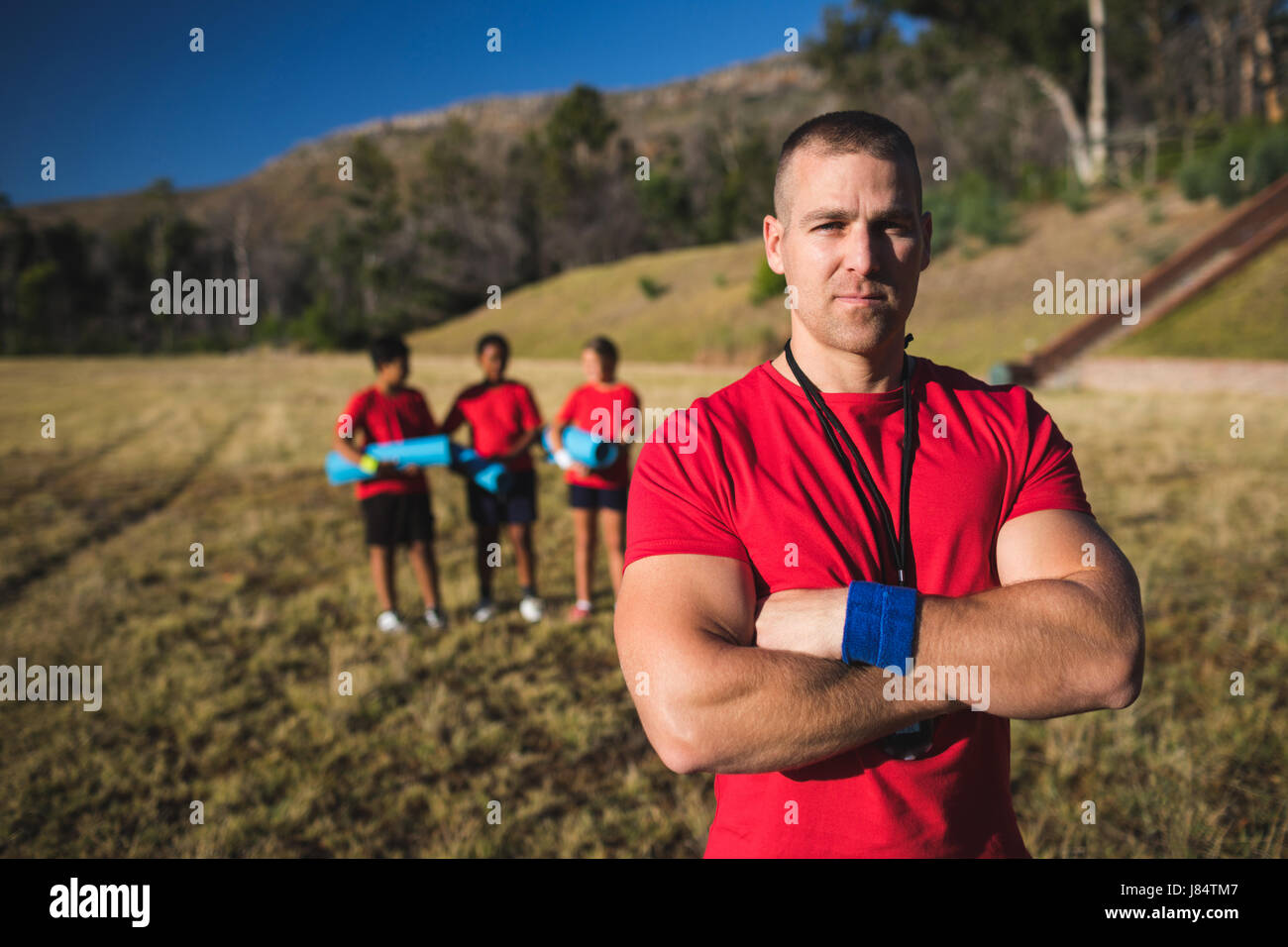 Portrait of trainer standing with arms crossed in the boot camp - Stock Image