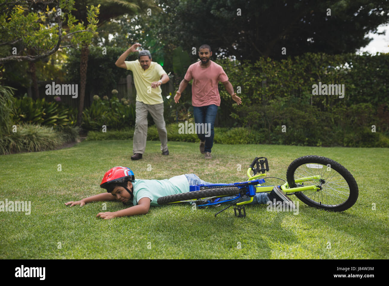 Grandfather and father running towards fallen boy with bicycle at park - Stock Image