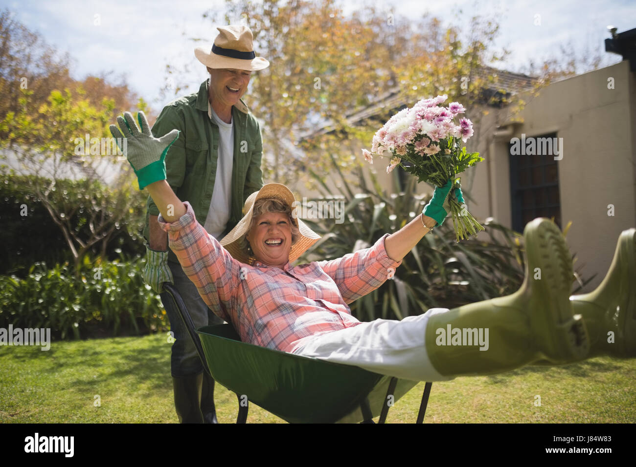 Man carrying cheerful senior woman holding bouquet in wheel borrow at backyard - Stock Image