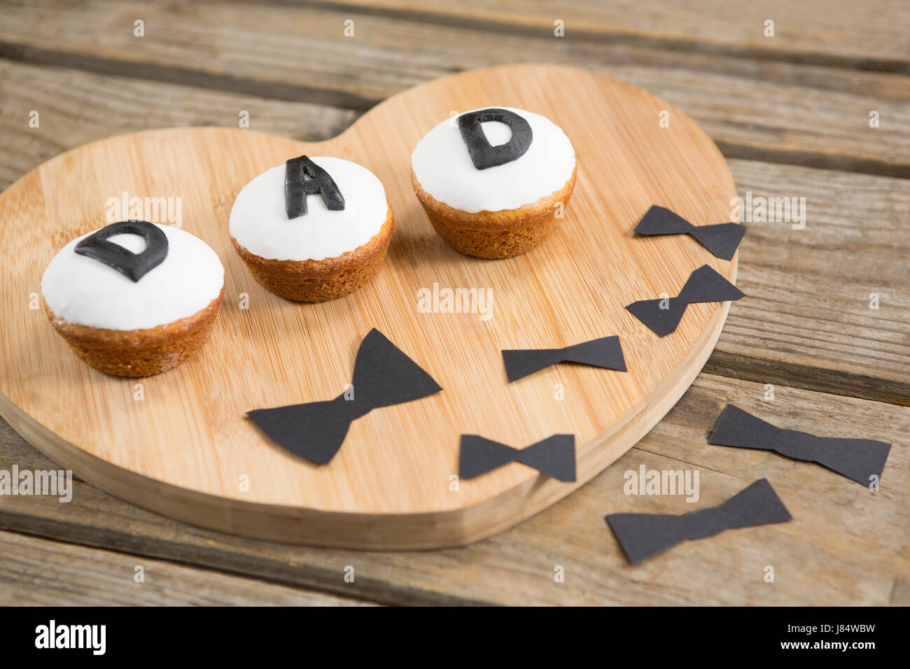 Close up of cupcakes with dad text by bow tie on wooden table - Stock Image