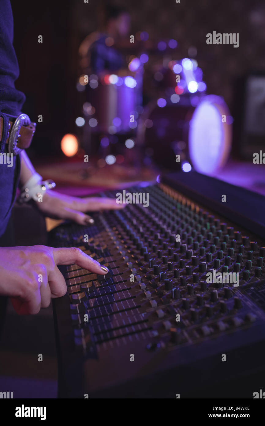 Mid section of female operating sound mixer in nightclub - Stock Image