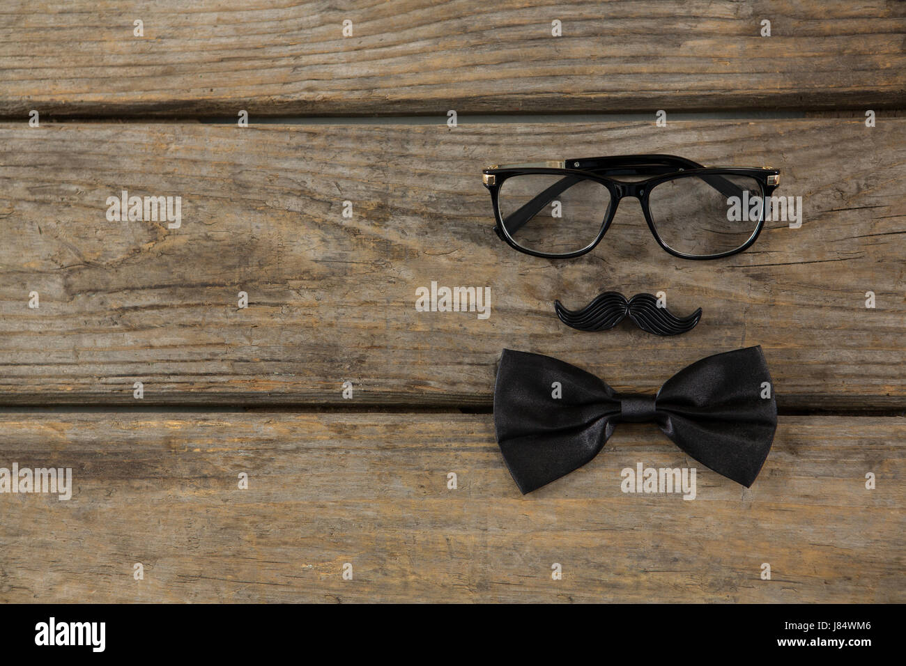 Overhead view of bow tie with mustache and eyeglasses on wooden table - Stock Image
