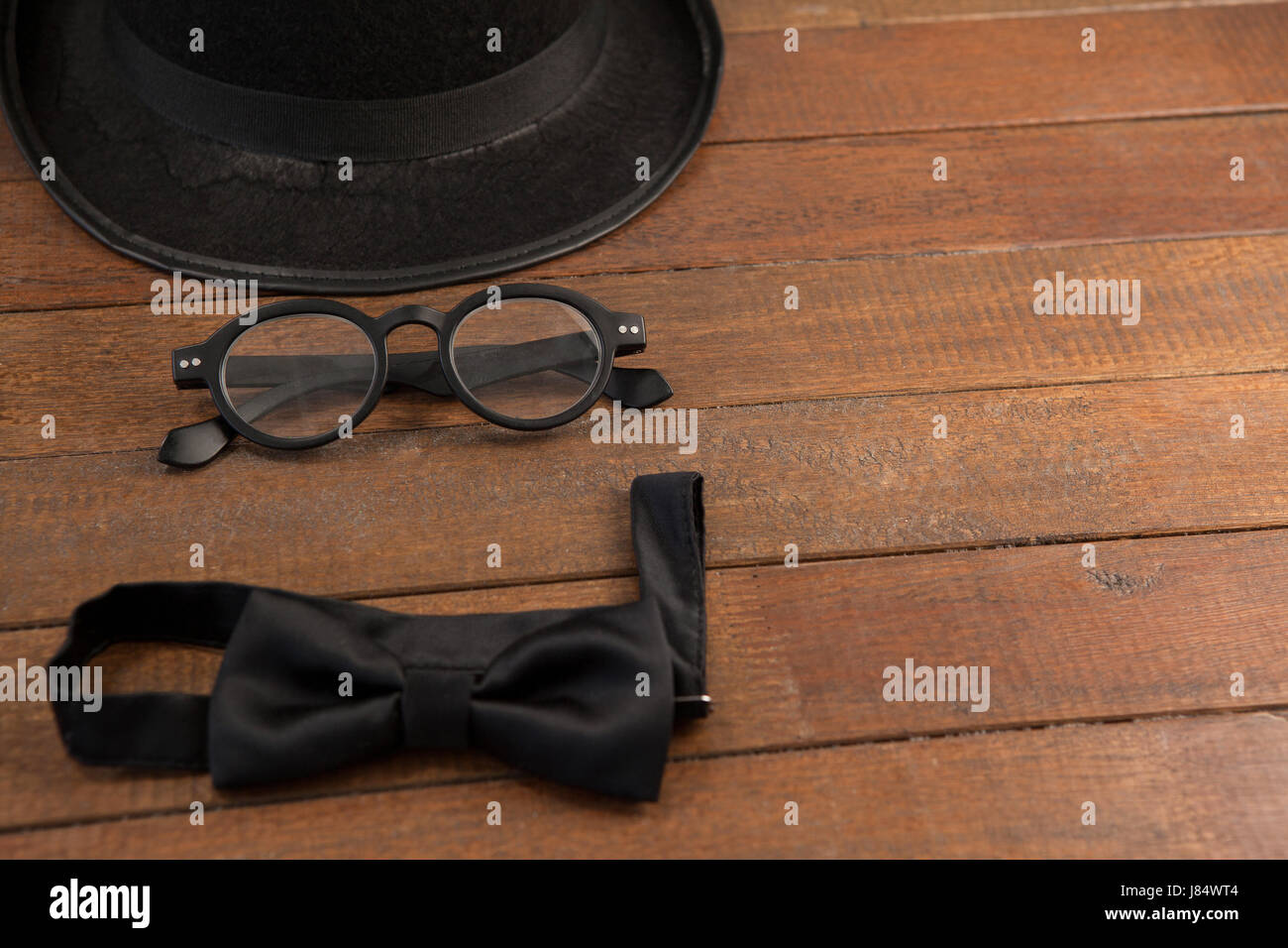 High angle view of hat with eyeglasses and bow tie on wooden table - Stock Image