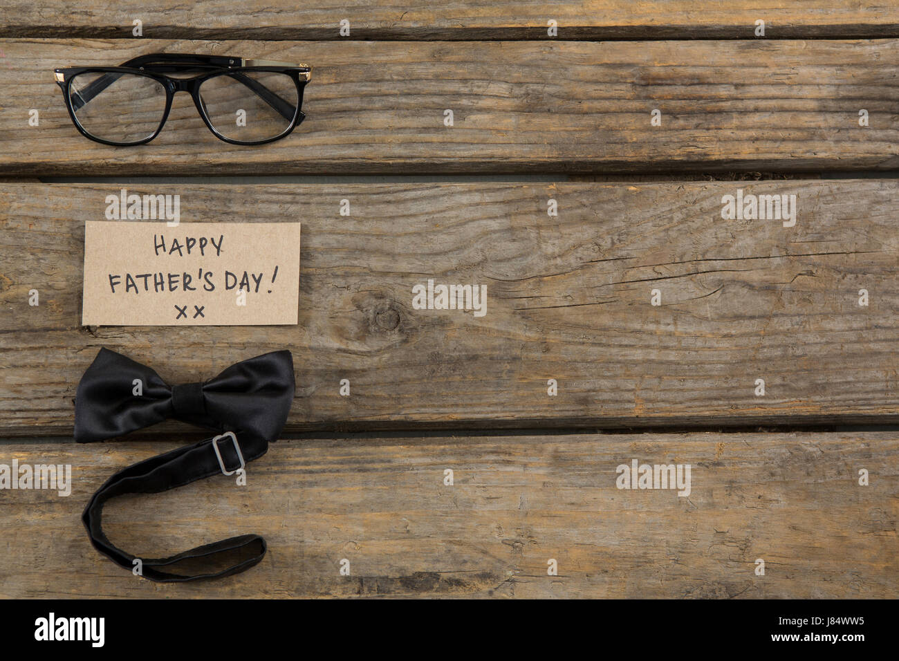 Overhead view of happy fathers day text by eyeglasses and bowtie on wooden table - Stock Image