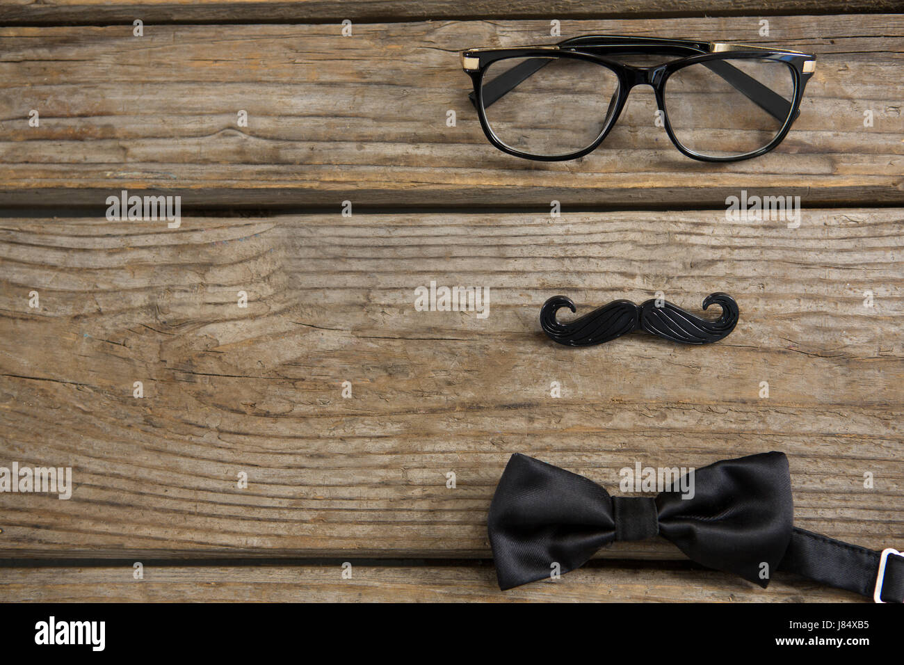 High angle view of mustache with eyeglasses and bow tie on wooden table - Stock Image