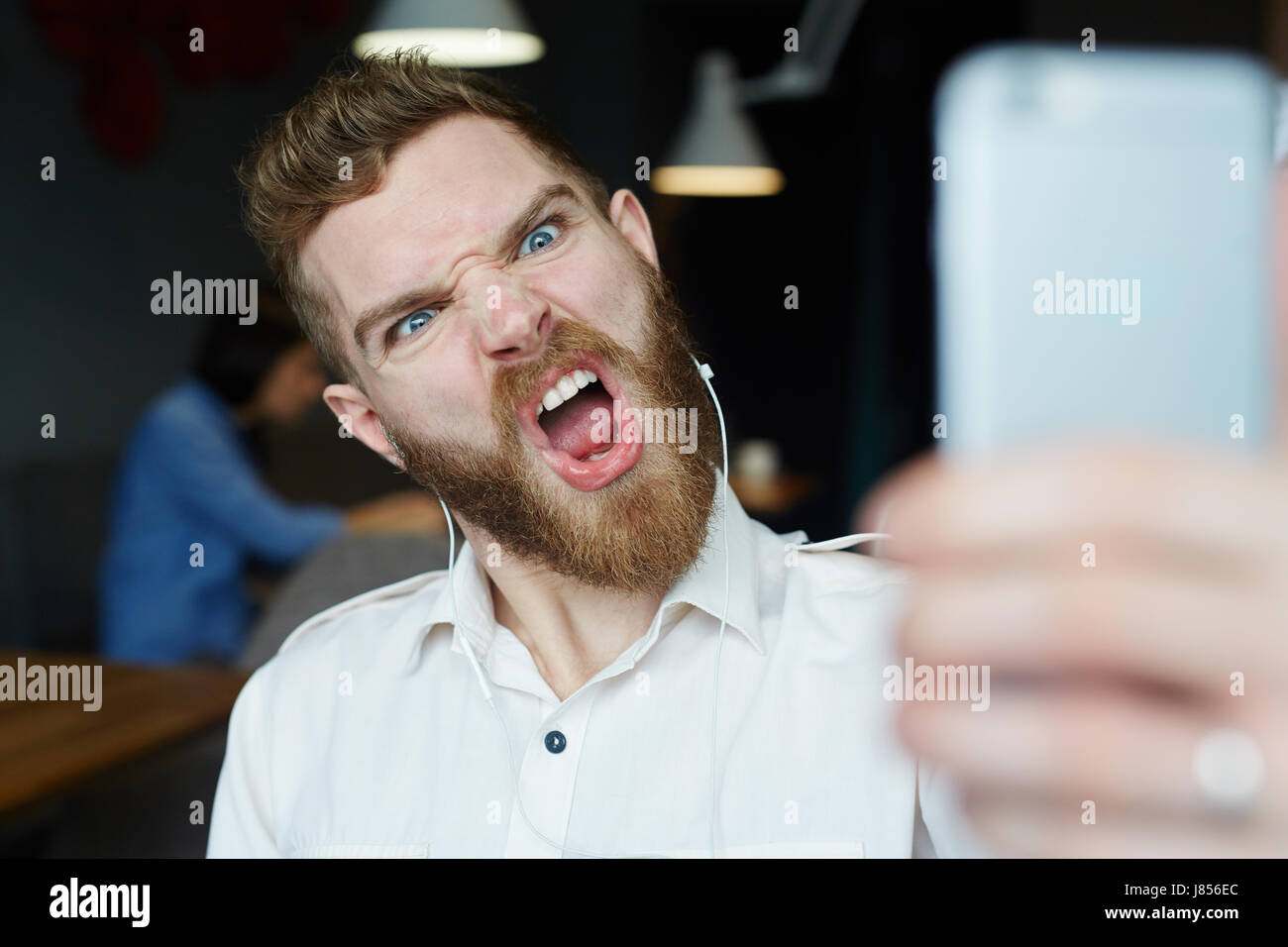 Portrait of modern bearded man yelling and grimacing angrily to camera posing for selfie photo - Stock Image